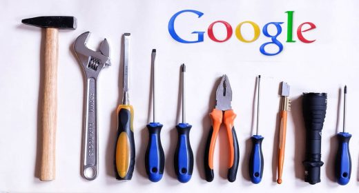 Selection of hand tools lined up underneath Google logo