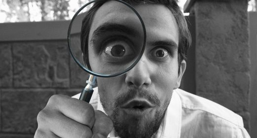 man looking at camera through a magnifying glass